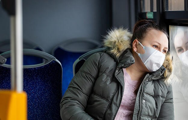 Woman rides bus wearing a mask